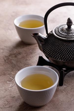 Traditioneller japanischer Kräutertee, gekocht in einem gusseisernen Kessel mit trockenen Bio-Kräutern. Alternative Medizin. Gesunder asiatischer grüner Tee.