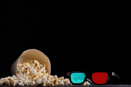 Snack for watching movies. A bucket of popcorn on a black background and 3 d glasses. Close-up.