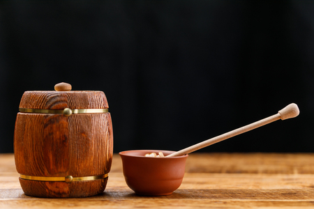 Barrel with honey and a spoon comb on a wooden table on a dark background. Close-up. Stock Photo