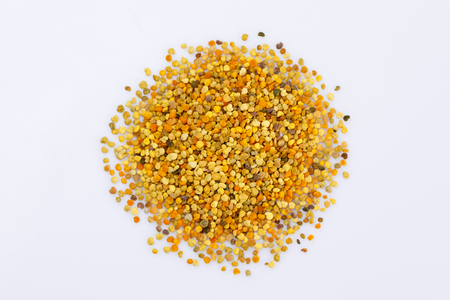A scattering of bee pollen on a white background. Bright pollen. Bee product. Close-up. Isolated.