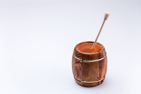 Wooden open barrel with fragrant liquid honey and honey stick on a white background. Close-up. Isolated. 免版税图像