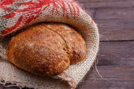 One craft bread on a wooden background. Close-up.