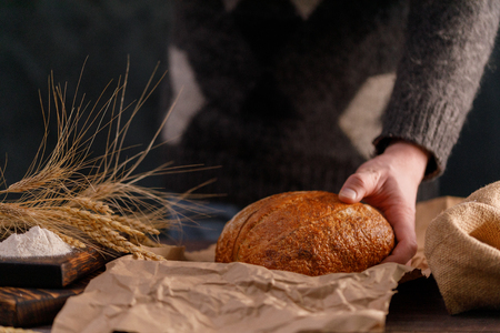 Craft bread closeup in man's hand. The concept of healthy food and traditional bakery. Rustic.