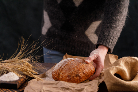 Homemade rye bread and spikelets close-up in a mans hand and flour is pouring. The concept of healthy food and traditional bakery. Rustic.
