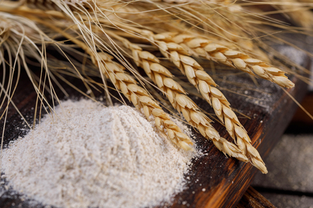 Spikelets and flour closeup on a wooden board. The concept of healthy food and traditional bakery. Rustic.