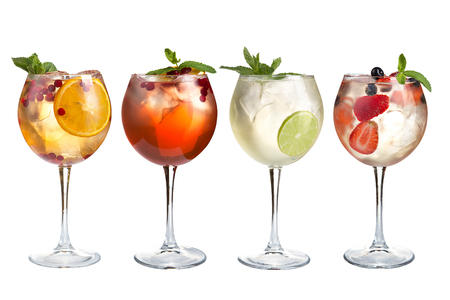 Alcoholic and non-alcoholic refreshing cocktails with mint, fruits and berries on a white background. Four cocktails in glass goblets. Isolated.