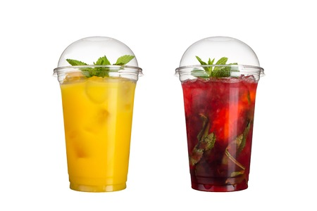 Delicious fruit smoothies in plastic cups, on a white background. Two cocktails with pineapple flavor and berry mojito. Isolated