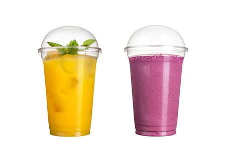 Delicious fruit smoothies in plastic cups, on a white background. Two cocktails with a taste of pineapple and wild berries. Isolated Stockfoto