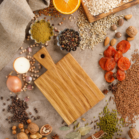 Dried fruits cereals spices and nuts organic healthy snacks on a textural background. The concept of healthy eating. Lenten products. Wooden decorative board with a place under the text. Copy space. Flat Lau.