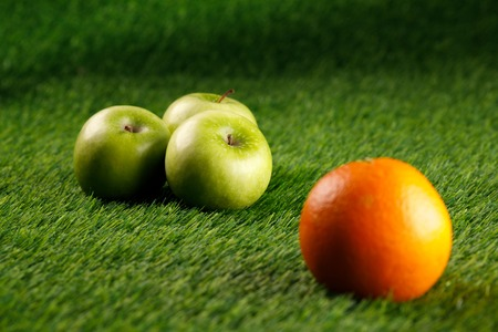 Abstract green background. Bush grass. Copy space. Place under the text.Three green apples and one orange.Close-up.