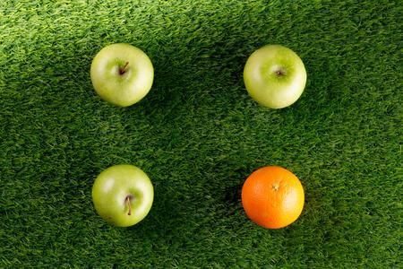 Fondo verde astratto. Erba di cespuglio. Copia spazio. Posto sotto il testo.Tre mele verdi e un'arancia.Quadrato di frutta. Archivio Fotografico
