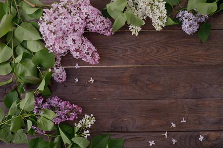 Decorazione di fiori sullo sfondo di assi di legno d'epoca. Sfondo vintage con fiori lilla e posto sotto il testo. Vista dall'alto. Disposizione piatta. Vintage ?. Archivio Fotografico