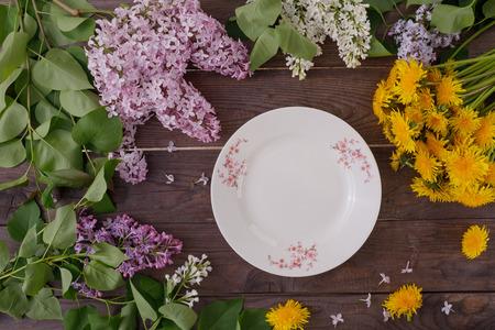Piatto e decoro di fiori sullo sfondo di assi di legno d'epoca. Sfondo vintage con fiori di tarassaco e lilla e un posto sotto il testo. Vista dall'alto. Disposizione piatta. Posate. Vintage ?.