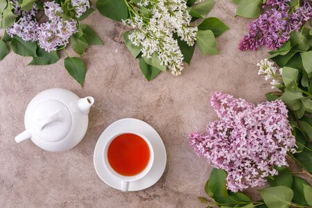 Tea set and flower decor on a textural background. Textural background with flowers and tea pair and place under the text. View from above. Flat lay. The concept of tea drinking. Vintage.
