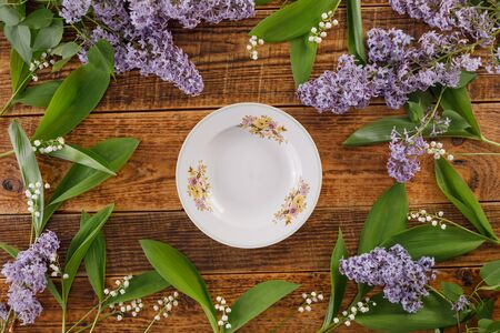 Plate and decor of flowers of lilies of the valley and lilac on the background of vintage wooden boards. Vintage background with flowers and place under the text. View from above. Flat lay. Cutlery. Vintage.