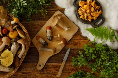 Mushrooms on old wooden background. Card on autumn or summertime. Forest harvest. Boletus, chanterelles, leaves, berries. Top view. Flat lay 写真素材