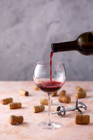 Red wine is poured into a glass. The concept of winemaking. Place under your text. Close-up.