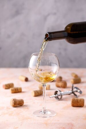 White wine is poured into a glass. The concept of winemaking. Place under your text. Close-up.