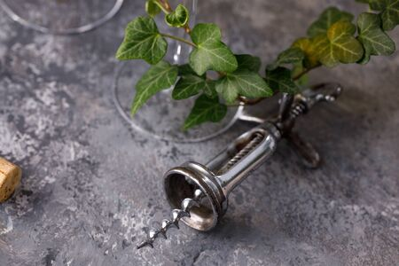 Exquisite vintage corkscrew for wine on a textural background. Copy space. Place for your text. Close-up. Archivio Fotografico - 127924420