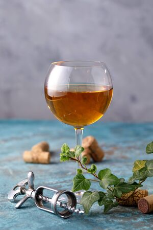 White wine in a glass. The concept of winemaking. Place under your text. Still life on a textural background. Close-up.
