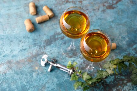Two glasses with white wine on a textural background. Copy space. Place for your text. Close-up. Banco de Imagens - 129268744
