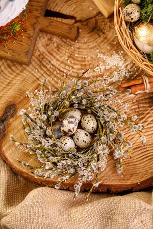 Easter still life. Wicker nest with eggs on a wooden saw. Traditional celebration concept. Close-up. Фото со стока