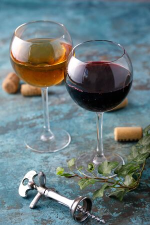 Glasses of white and red wine. The concept of winemaking. Place under your text. Still life on a textural background. Close-up. Banco de Imagens - 129273793