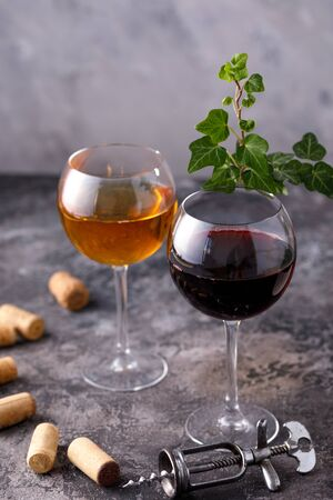 Glasses of white and red wine. The concept of winemaking. Place under your text. Still life on a textural background. Close-up. Banco de Imagens - 129275201