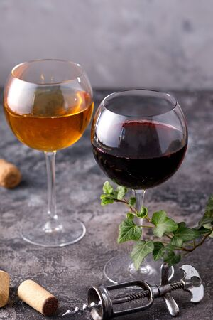Glasses of white and red wine. The concept of winemaking. Place under your text. Still life on a textural background. Close-up. Banco de Imagens