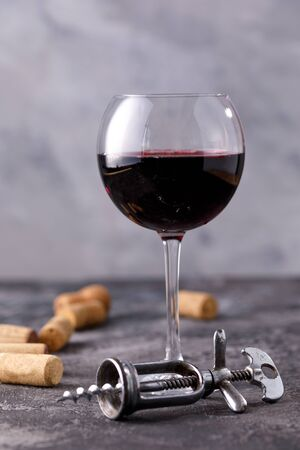 A glass with red wine. The concept of winemaking. Place under your text. Still life on a textural background. Close-up.