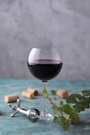 A glass with red wine. The concept of winemaking. Place under your text. Still life on a textural background. Close-up. Archivio Fotografico - 129275216