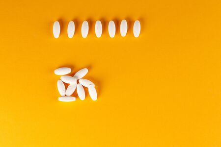 A scattering of white oval-shaped tablets on an orange background. Close-up.