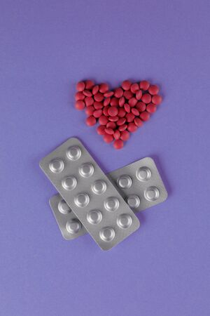 Packing pills. A scattering of red pills in the form of a heart on a purple background. Close-up.