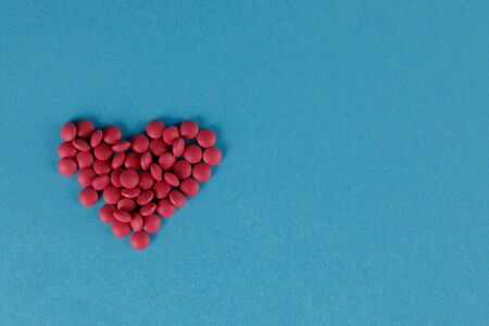 A scattering of red pills in the form of a heart on a blue background. Close-up.