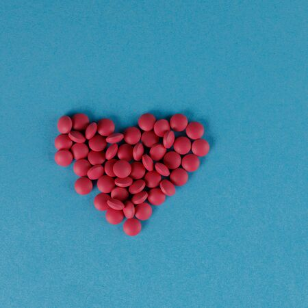 A scattering of red pills in the form of a heart on a blue background. Square. Close-up.