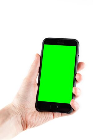 Touch screen smartphone in a hand.Man holding smartphone with blank screen on white background, closeup of hand. Space for text.Green screen.