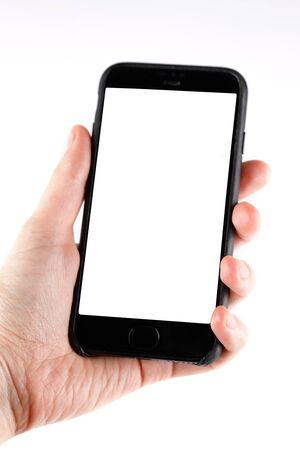 Smartphone à écran tactile dans une main. Homme tenant un smartphone avec écran blanc sur fond blanc, gros plan de la main. Espace pour le texte.