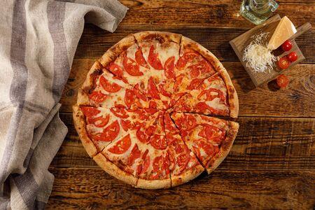 Pizza Margherita su un tavolo di legno. Natura morta con ingredienti. Vista dall'alto.