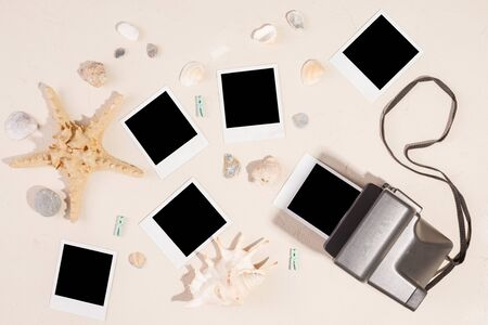 Empty photos and camera on a textural background. The concept of preserving memories. Starfish and shells. Copy space.