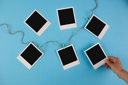 Instant photo frames on a blue background. Concept of preservation of memories. Flat lay. Copy space.