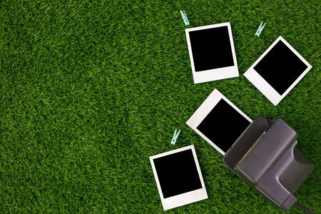 Instant photo frames and a camera on a background of lawn grass. Concept of preservation of memories. Flat lay. Copy space. Banco de Imagens