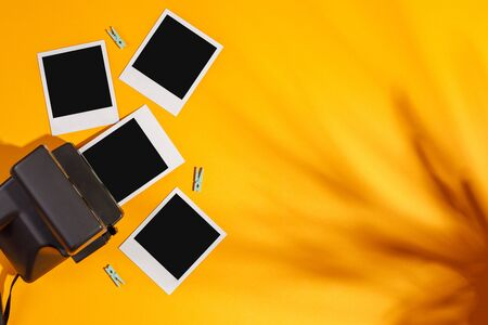 Instant photo frames and camera on a yellow background. Concept of preservation of memories. Flat lay. Copy space. Banco de Imagens