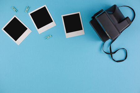 Instant photo frames and camera on a blue background. Concept of preservation of memories. Flat lay. Copy space.