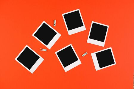 Instant photo frames and camera on a red background. Concept of preservation of memories. Flat lay. Copy space.