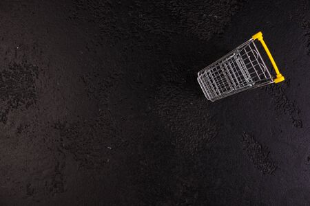 Shopaholic. Buyer. Shopping concept. Close-up. From above. Isolated shopping trolley on a black texture background. Copy space.