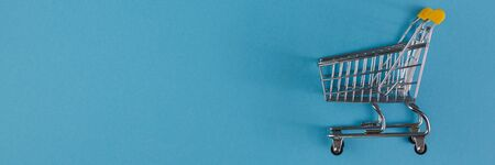 Shopaholic. Buyer. Shopping concept. Close-up. From above. Isolated shopping trolley on a blue background. Copy space. Stock Photo