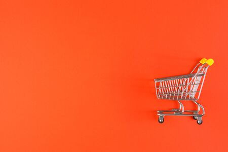 Shopaholic. Buyer. Shopping concept. Close-up. From above. Isolated shopping trolley on a red background. Copy space.