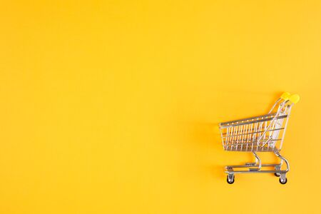 Shopaholic. Buyer. Shopping concept. Close-up. From above. Isolated shopping trolley on a yellow background. Copy space.