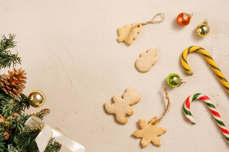 Christmas caramel canes and cookies on a textured background. Happy new year background, composition of christmas decorations. Holiday concept. Flat lay.
