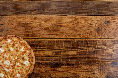 Pizza with salmon and cheese on a wooden background. Close-up. The concept of delicious food. View from above. Copy space. Stockfoto